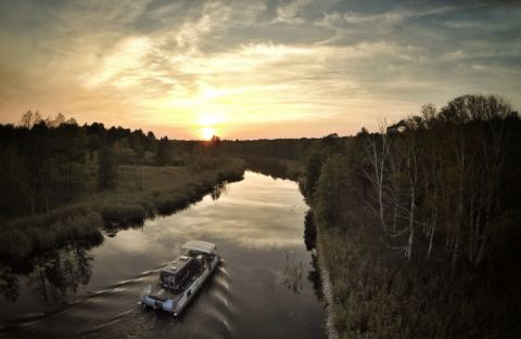 Ein freecamper mit Wohnmobil fährt auf  der Havel dem Sonnenaufgang entgegen.