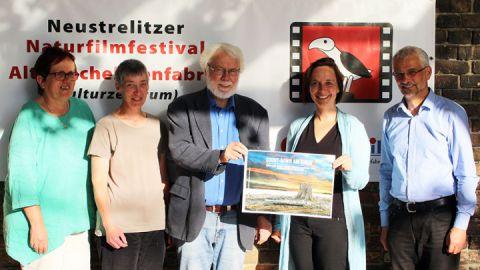 """Veranstalter des 9. Neustrelitzer Filmfestivals mit dem Plakat des Gewinnerlangfilms """"Countdown am Xingu"""""""